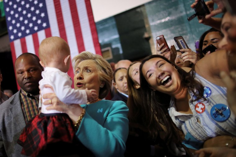Image: Democratic U.S. presidential nominee Hillary Clinton holds a baby during a campaign rally in Lake Worth, Florida