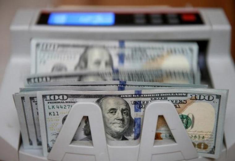 Money counter counts 100 U.S dollar banknotes in Kiev