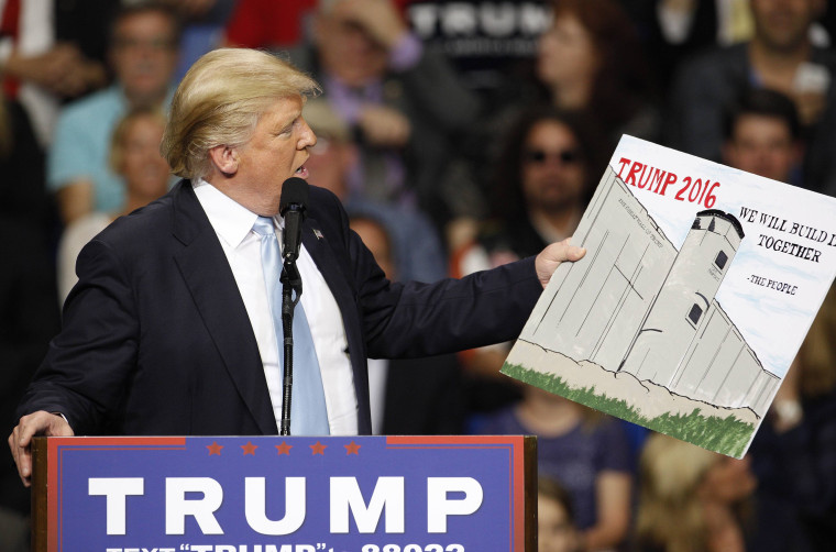 Image: U.S. Republican presidential candidate Donald Trump holds a sign supporting his plan to build a wall between the United States and Mexico that he borrowed from a member of the audience at his campaign rally in Fayetteville North Carolina