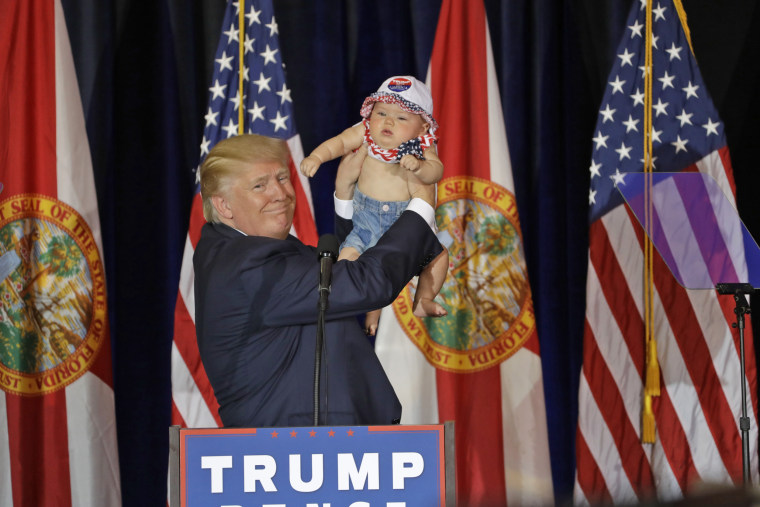 Republican presidential candidate Donald Trump holds up 6-month-old Catalina Larkin of Largo, Florida, on Nov. 5 in Tampa.