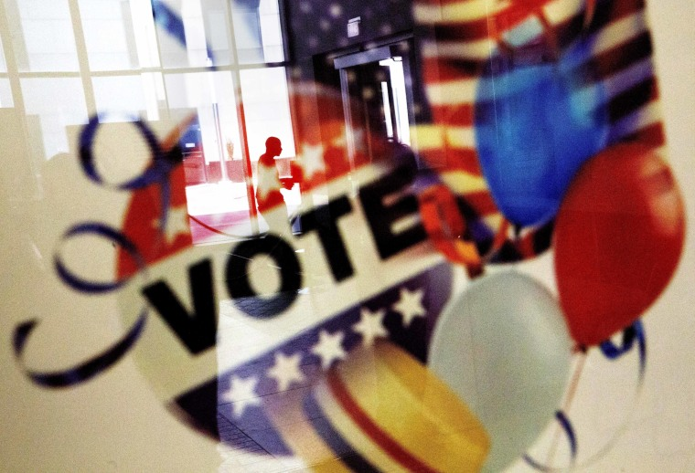 Image: A voter is reflected in the glass frame of a poster while leaving a polling site in Atlanta