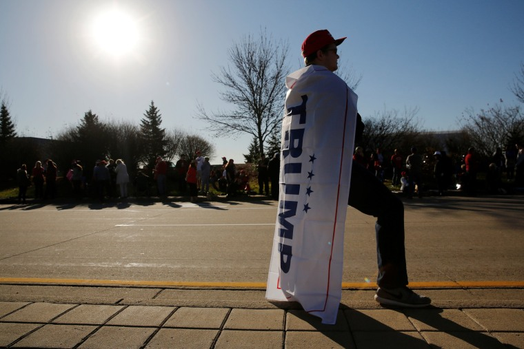 Image: Supporters stand in line as they arrive to attend a rally with Trump in a cargo hangar at Minneapolis Saint Paul International Airport in Minneapolis