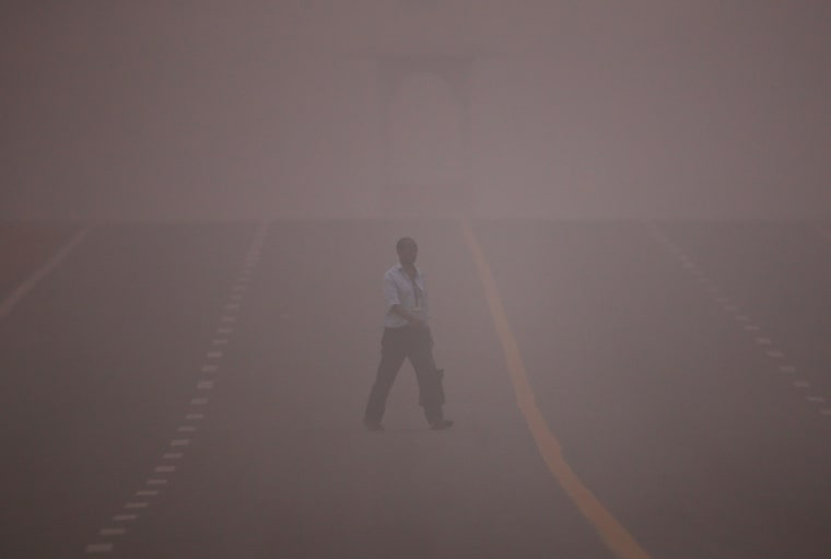 Image: A man crosses a road amidst the heavy smog in New Delhi