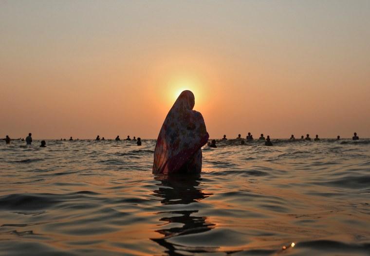 Image: Hindu devotees worship the Sun god in the waters of the Arabian Sea during Chhath Puja in Mumbai