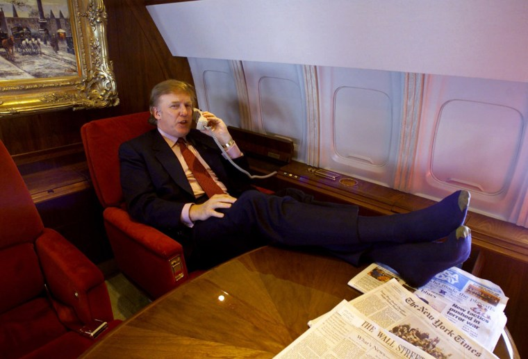 Image: Trump uses the phone and puts his feet on the table in his private plane