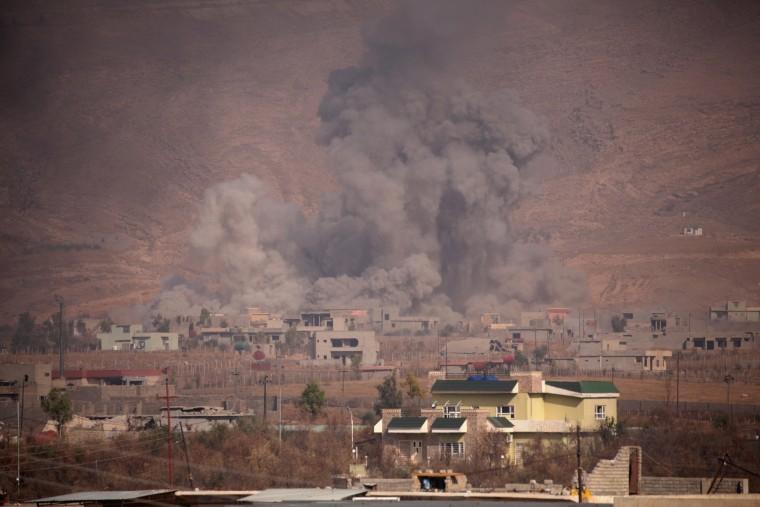 Image: Smoke rises during clashes between Peshmerga forces and ISIS militants in Bashiqa, Iraq