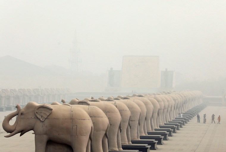 Image: People walk inside the Ambedkar Memorial Park amidst heavy smog in Lucknow