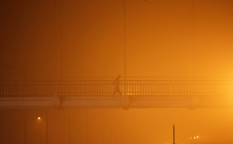 Image: A man walks on a pedestrian bridge amidst the heavy smog in New Delhi