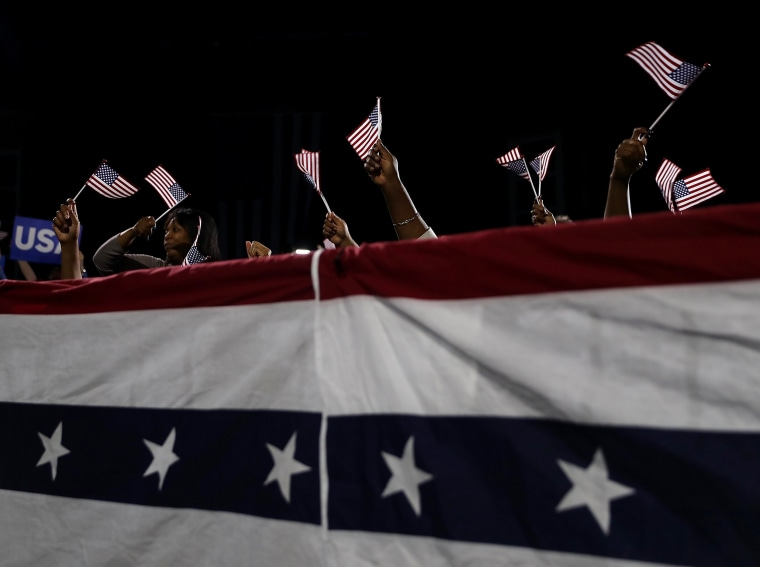 Image: Supporters hold American flags at a rally for Hillary Clinton