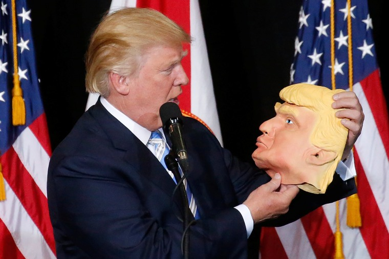 Image: Republican presidential nominee Donald Trump looks at a mask of himself as he speaks during a campaign rally in Sarasota