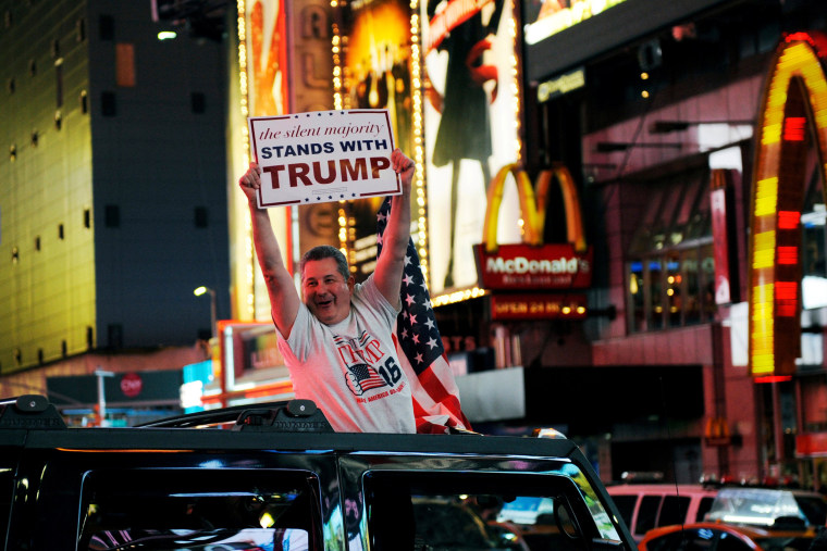 Image: A man leans out of a Hummer shouting words in support of U.S. Republican presidential nominee Donald Trump while driving through Times Square in New York
