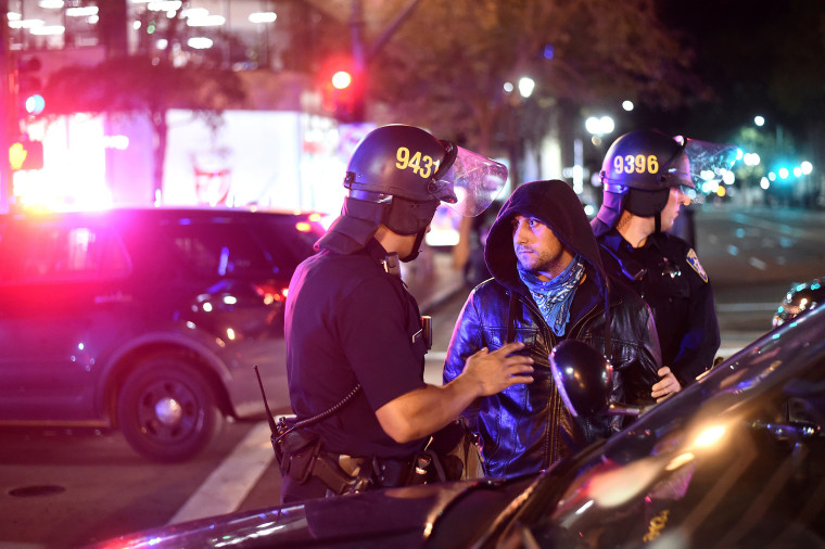 Image: Police detain a protester marching against president-elect Donald Trump in Oakland