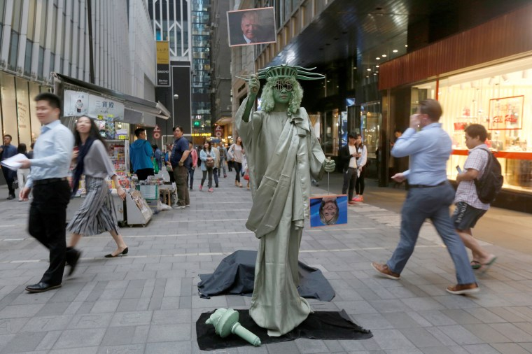 Image: A street performer dressed as the Statue of Liberty in Hong Kong