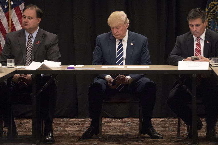 Image: Donald Trump is interrupted by a phone call during a meeting with specialists on the problem of opiate addiction, after a campaign event in Manchester, N.H.