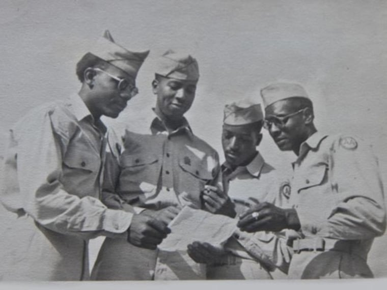 Wilson Monk (third from left) and other men from the 320th appear to be in deep thought as they peruse a document.