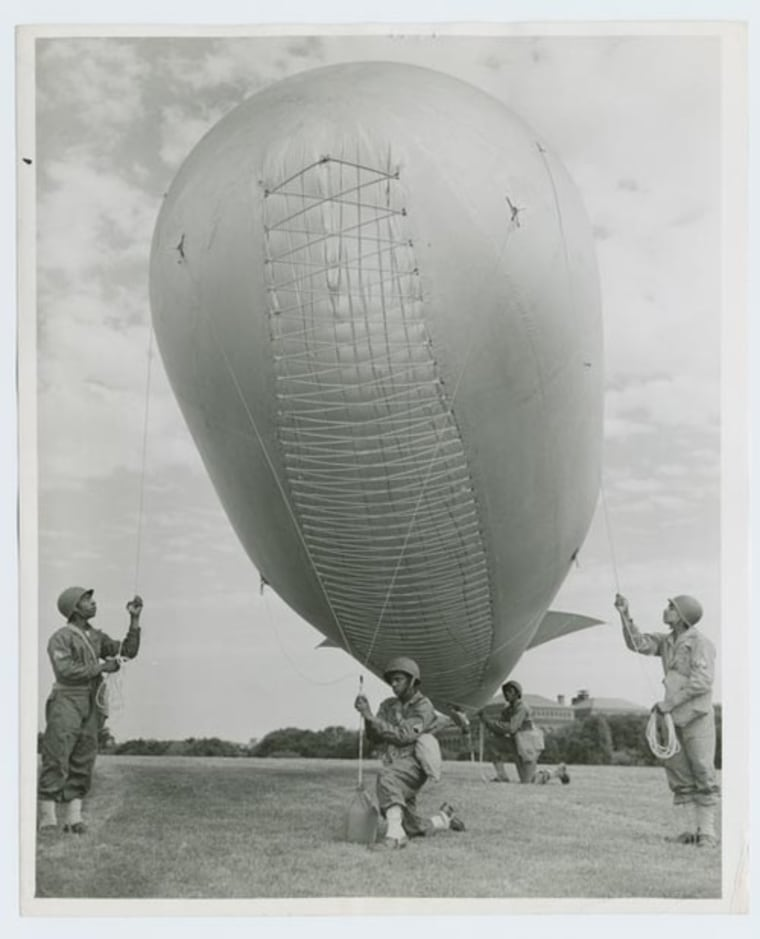 "A crack Negro barrage balloon unit from Camp Tyson, Tenn., is one of the many features of the mammoth ""BACK THE ATTACK"" Army show now sparking $15,000,000,000, Third War Loan Drive in Washington D. C.; Members of the unit demonstrate how barrage balloons are used to protect ships, installations, bridges and cities from strafing by low-flying enemy planes."" Roger Smith; Schomburg Center for Research in Black Culture, Photographs and Prints Division, The New York Public Library."