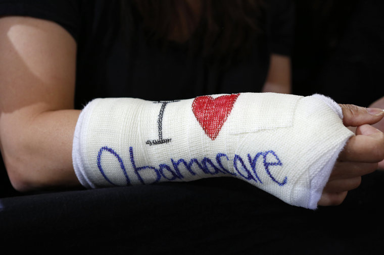 "Image: Cathey Park of Cambridge, Massachusetts wears a cast for her broken wrist with ""I Love Obamacare"""