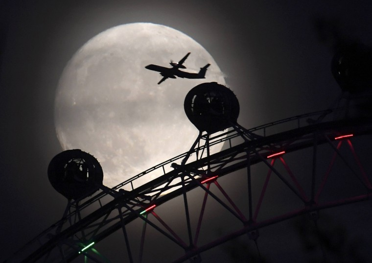 """Image: An aeroplane flies past the London Eye wheel, and moon, a day before the \""""supermoon\"""" spectacle in London"""