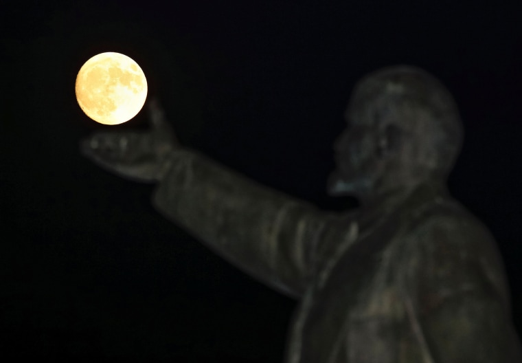 "Image: A full moon rises behind a statue of Soviet state founder Vladimir Lenin on the eve of the ""supermoon"" spectacle, Baikonur"