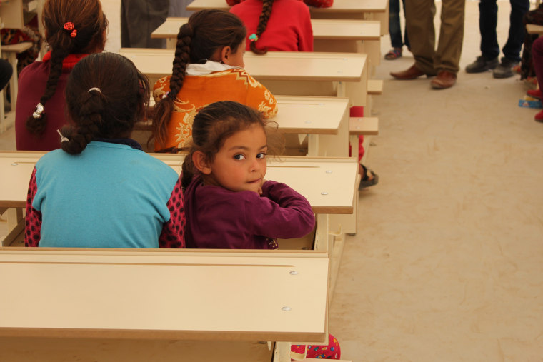 Image: A young student in a makeshift classroom at the Debaga camp