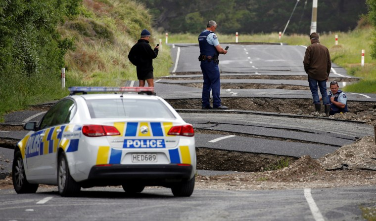 Image: Policemen and locals look at damage following an earthquake, along State Highway One near the town of Ward, New Zealand