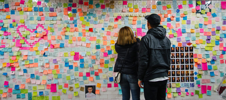 Image: People look at post-it notes covering a wall as part of the art piece 'Subway Therapy' at the Union Square subway station in Manhattan