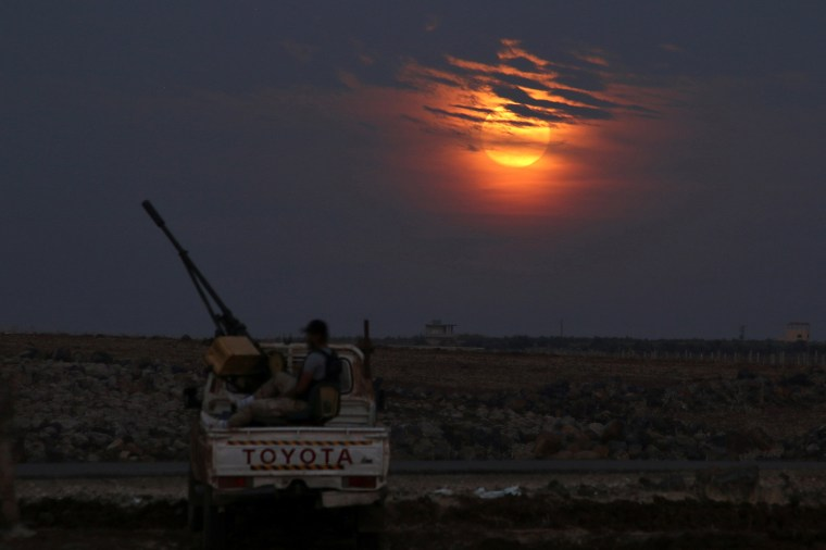 Image: A Free Syrian army fighter sits on a pick-up truck mounted with a weapon, as the supermoon partly covered by clouds is seen in the background, in the west of the rebel-held town of Dael