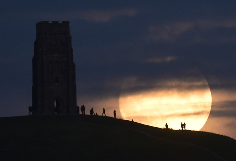 "Image: The moon rises near Glastonbury Tor a day before the ""supermoon"" spectacle, in Glastonbury"