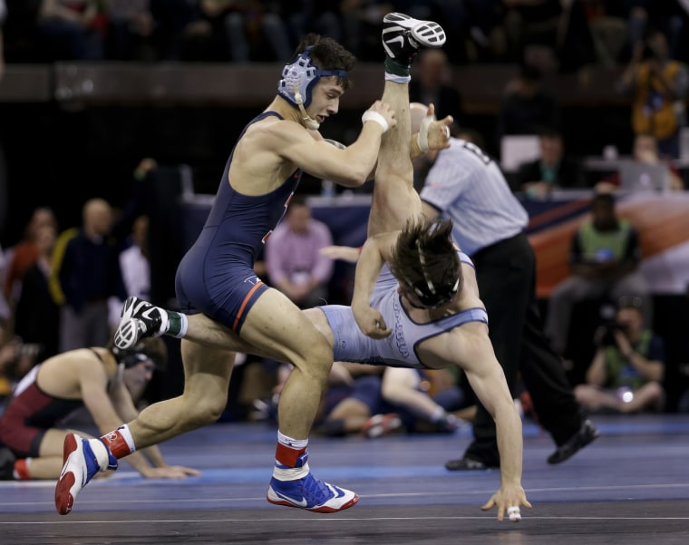 Illinois' Isaiah Martinez, left, takes down Columbia's Markus Scheidel in a 157-pound weight class match during the second round of the NCAA Divison I Wrestling Championships, March 17, in New York.