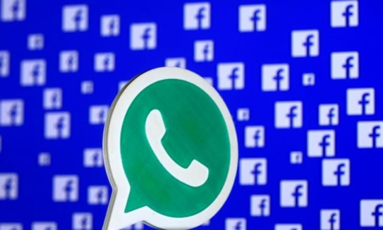 A 3D printed Whatsapp  logo is seen in front of a displayed Facebook logo in this illustration taken