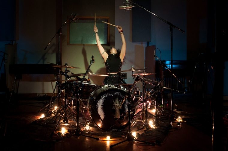 Andrea Alvarez playing drums at a concert.