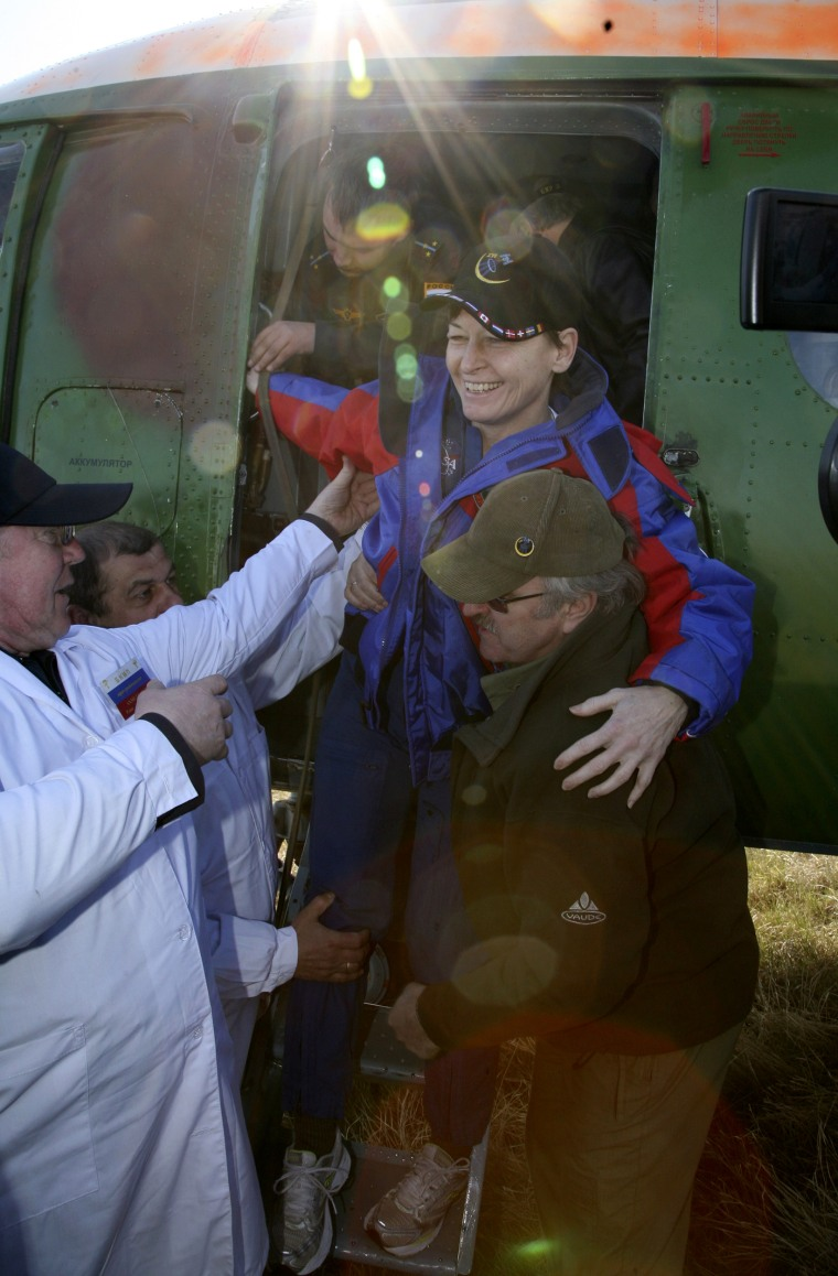 Image: Ground crew help U.S. astronaut Whitson after landing in northern Kazakhstan