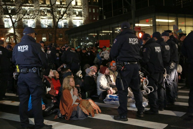 """More than 39 peaceful protesters were arrested for linking arms and then sitting in the middle of Lafayette Street in lower Manhattan. The NYPD warned the protesters - who were praying, singing, and chanting """"water is life"""" - that they would be arrested for disorderly conduct if they refused to move. Nov. 15."""