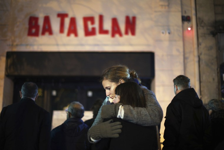 Women hug in front of the Bataclan concert hall in Paris, Sunday, Nov. 13, 2016. France marked the anniversary of Islamic extremists' coordinated attacks on Paris with a somber silence broken only by voices reciting the names of the 130 people killed.