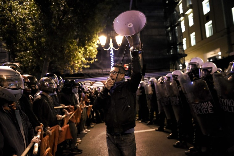 Image: A man speaks into a megaphone as demonstrators hold red flags during a protest against the visit of the US president