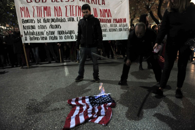Image: Protestors burn a US flag during a demonstration against the visit of the US president
