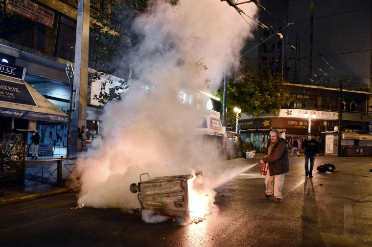 Image: A man tries to estinguish a garbage bins set on fire by protesters