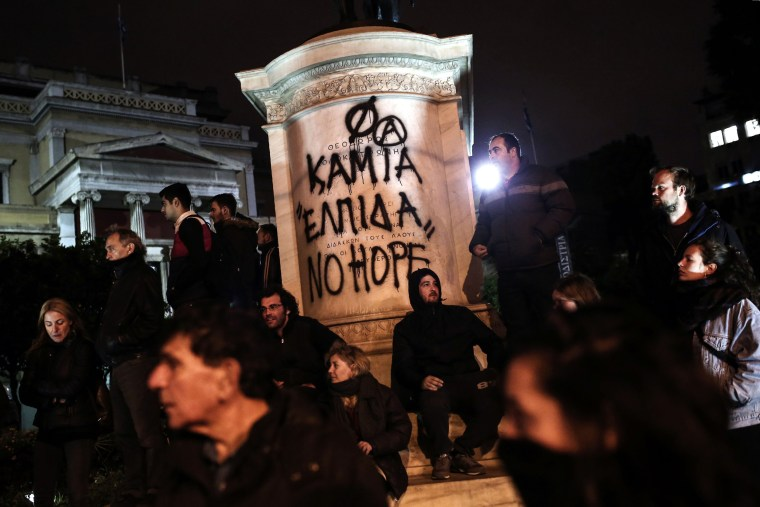 Image: Protesters stand in front of a graffiti that reads 'No Hope' as they demonstrate against the visit of the US president