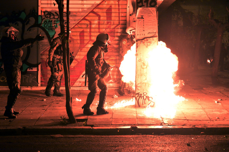 Image: Fire from a molotov cocktail rises near Greek riot police during clashes around the Polytechnic school
