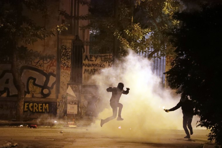 Image: A protester jumps to avoid tear gas as another one prepares to throw a firebomb during a protest against the visit of US President Barack Obama