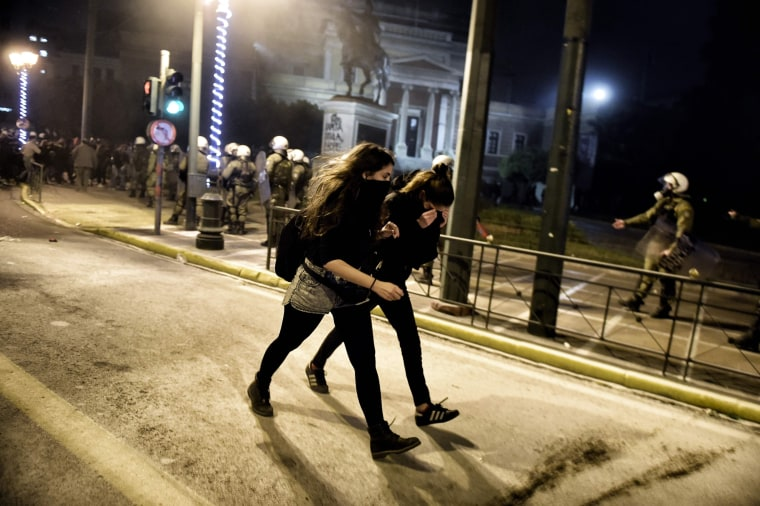 Image: Demonstrators cover their faces and disperse after tear gas was fired during clashes with Greek riot police