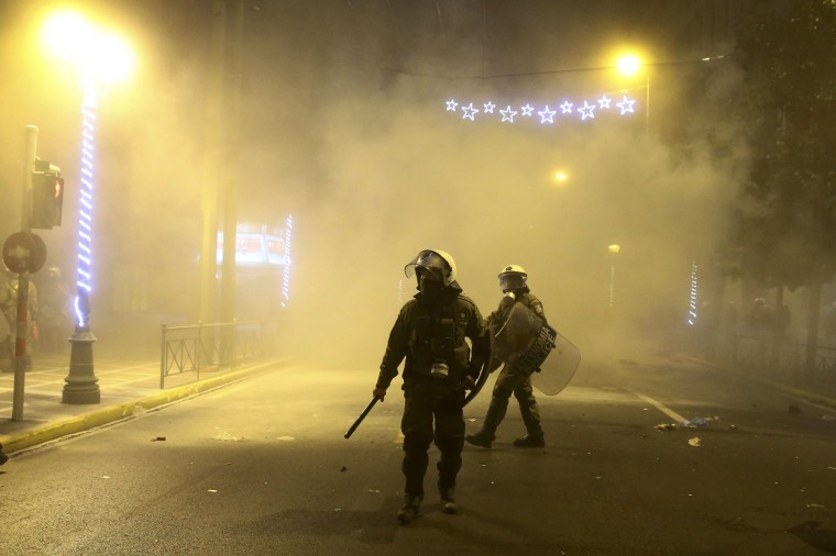 Image: Riot police stands on a street amid teargas during a demonstration against the visit of US President Obama in Athens