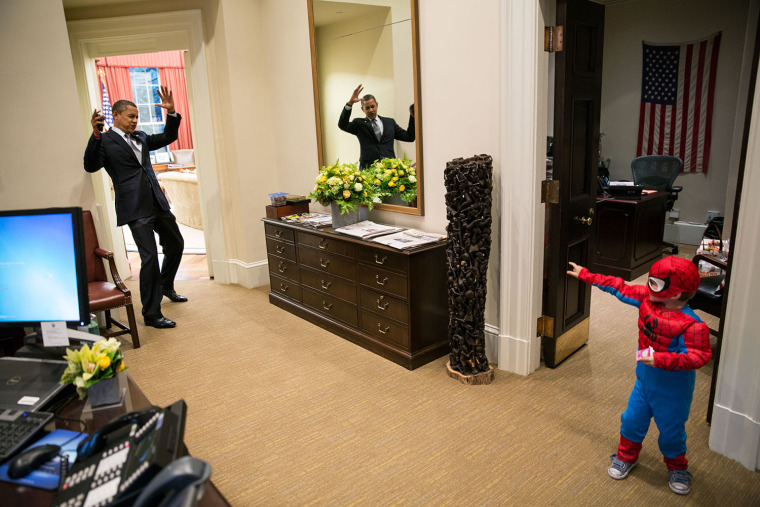 """President Obama pretends to be caught in Spider-Man's web as he greets Nicholas Tamarin, 3, just outside the Oval Office on Oct. 26, 2012. Spider-Man had been trick-or-treating for an early Halloween with his father, White House aide Nate Tamarin in the Eisenhower Executive Office Building. \""""I can never commit to calling any picture my favorite, but the president told me that this was HIS favorite picture of the year when he saw it hanging in the West Wing a couple of weeks later.\"""""""