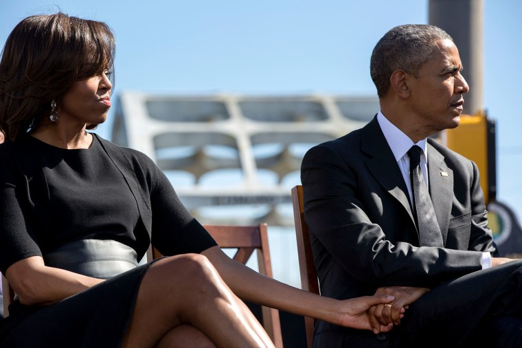 President Barack Obama and first lady Michelle Obama hold hands as they listen to Rep. John Lewis, D-Ga., during an event to commemorate the 50th Anniversary of Bloody Sunday and the Selma to Montgomery civil rights marches, at the Edmund Pettus Bridge in Selma, Alabama, March 7, 2015.