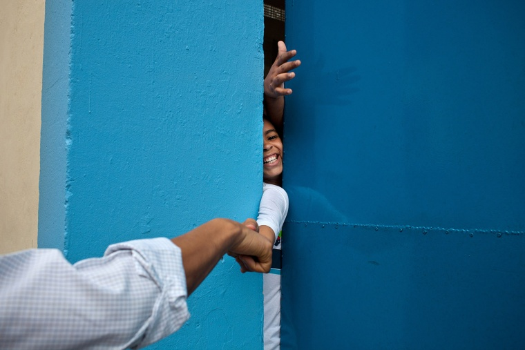 Despite security concerns, the president decided to walk into the street to wave to people gathered outside the Cidade de Deus favela community center in Rio de Janeiro. As he was walking, a young boy reached out of a closed door and the president reached over to give him a fist bump on March 20, 2011.