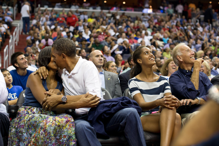 """President Barack Obama kisses First Lady Michelle Obama for the \""""Kiss Cam\"""" while attending the U.S. Men's Olympic basketball team's game against Brazil at the Verizon Center in Washington, D.C., July 16, 2012. Vice President Joe Biden and Malia Obama look up at the jumbotron."""