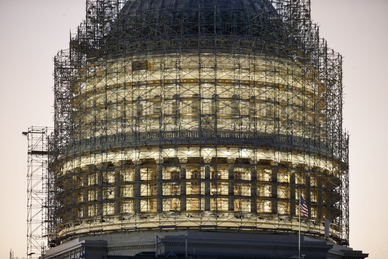 Image: The Capitol Dome is nearly obscured by scaffolding at dawn in Washington