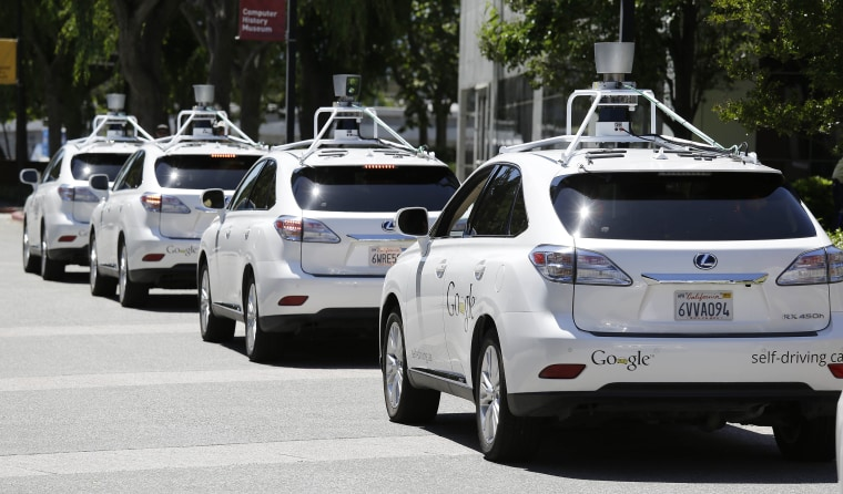 Image: A row of Google self-driving cars are shown outside the Computer History Museum in Mountain View, Calif.