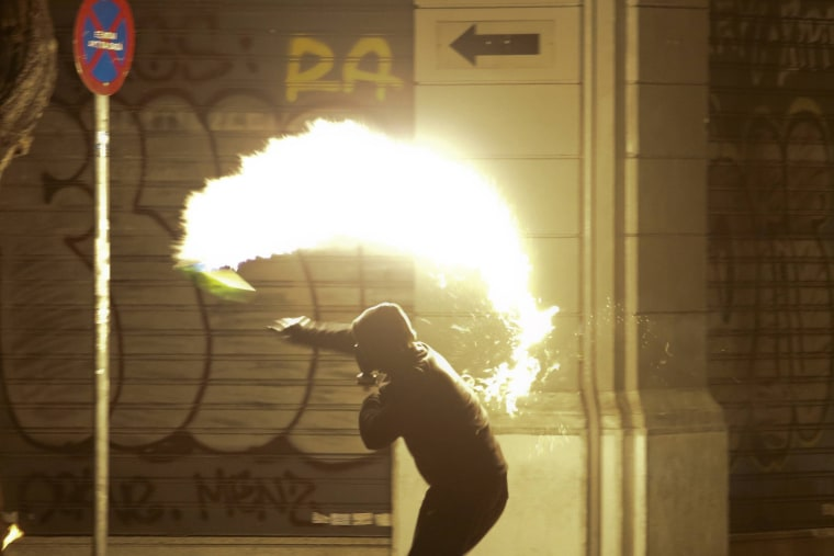 Image: A hooded protester throws a petrol bomb to riot policemen during clashes, following a rally marking the 43rd anniversary of a 1973 student uprising against the military dictatorship that was ruling Greece, in Athens