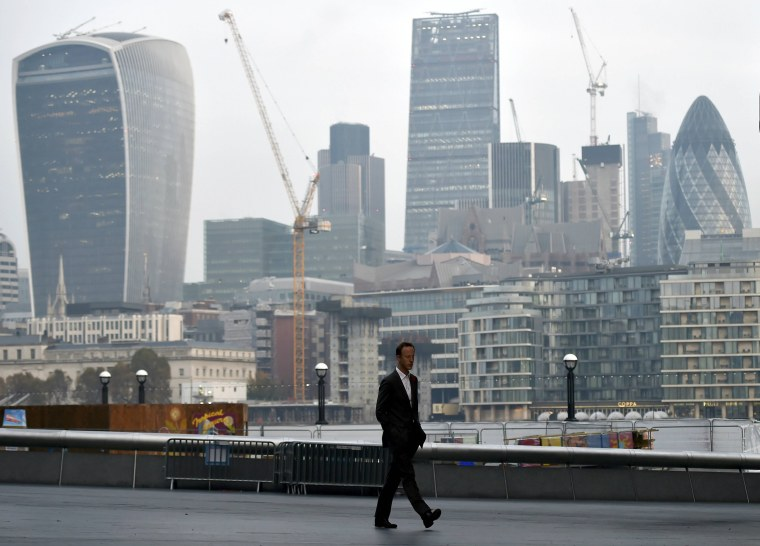 Image: A man walks in front of the City of London financial district of London